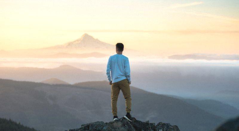 молодой человек на вершине горы