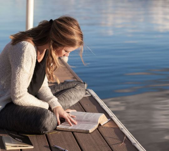 девушка с книгой на берегу озера