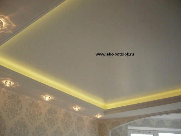 Двухуровневый натяжной потолок в спальной комнате установлен в Ленинградской области рядом с городом Санкт-Петербург. На фото виден натяжной потолок произведенный и установленный компанией ABC-POTOLOK. Белый матовый натяжной потолок второго уровня с светодиодной подсветкой, расположенной на закарнизной нише первого уровня по периметру комнаты и встроенными светильниками со светодиодными лампами MR 16