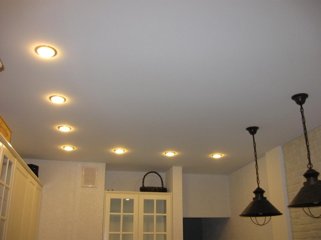 Белый матовый натяжной потолок в интерьере с люстрой и светильниками
